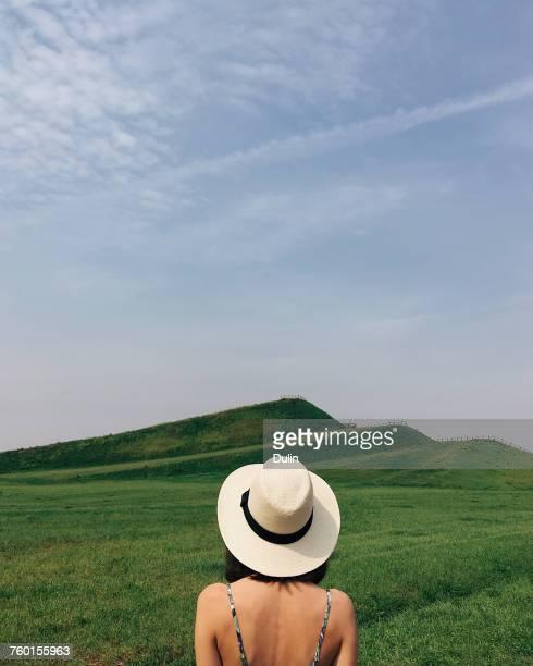 rear view of a woman wearing a straw hat standing in a rural landscape, minsk, belarus - femme au chapeau photos et images de collection