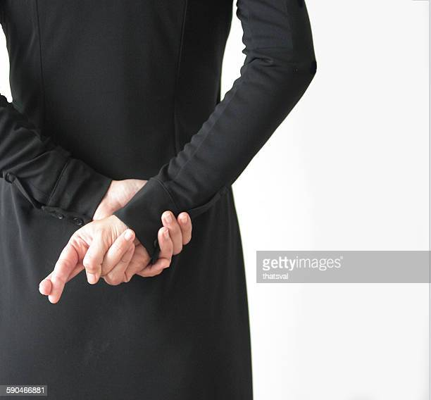 Rear view of a woman with fingers crossed behind back