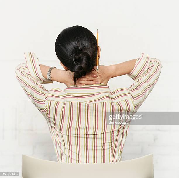 rear view of a woman with her hands on her neck - bad posture stock pictures, royalty-free photos & images