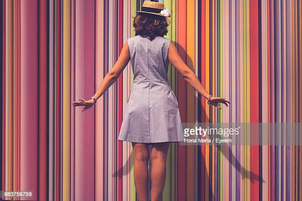rear view of a woman with multi colored curtain - striped dress stock photos and pictures