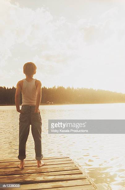 Rear View of a Young Boy Standing on the Edge of a Pier in Summer