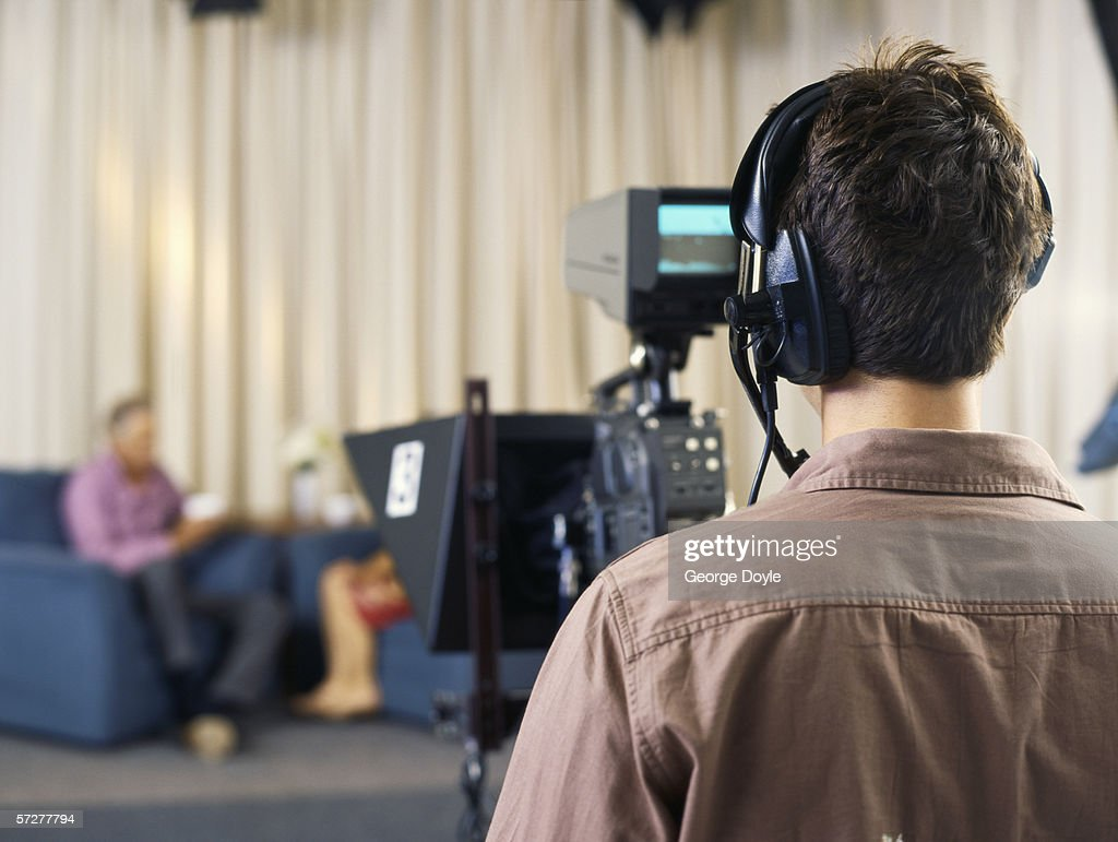 Rear view of a young cameraman working in a tv studio : Stock Photo