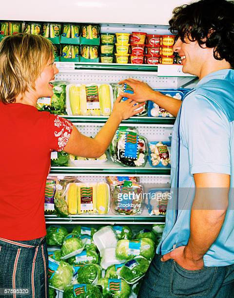 Rear view of a young couple picking food from shelves in cold storage