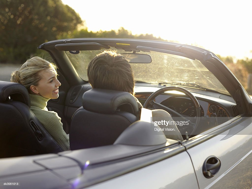 Rear View of a Young Couple Sitting in the Front Seat of a Convertible, Smiling at Each Other : Stock Photo