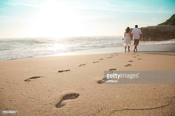 Rear view of a Young couple walking barefoot on the beach at sunset, Laguna Beach, Orange County, California, USA