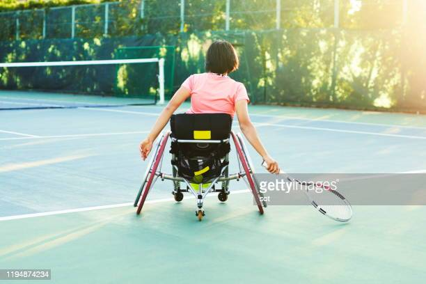 rear view of a young female in a wheelchair playing tennis on a tennis court - 車いすテニス ストックフォトと画像