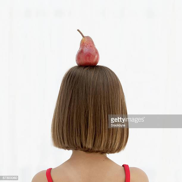 Rear view of a young girl (8-9) balancing a pear on her head