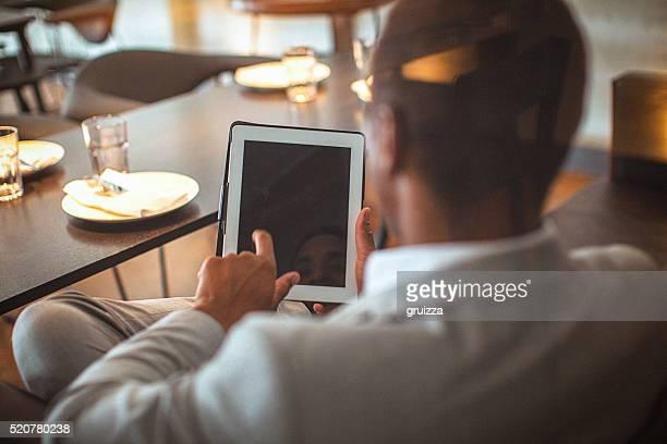 Hinterer Ansicht eines jungen gut aussehend Geschäftsmann halten Tablet