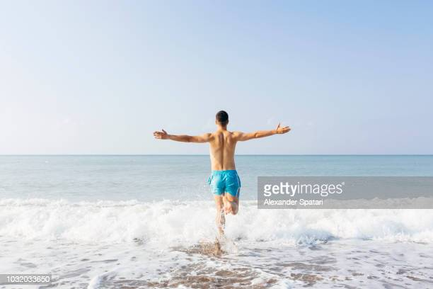 rear view of a young happy man with arms outstretched running towards the sea on a sunny day - homem costas imagens e fotografias de stock