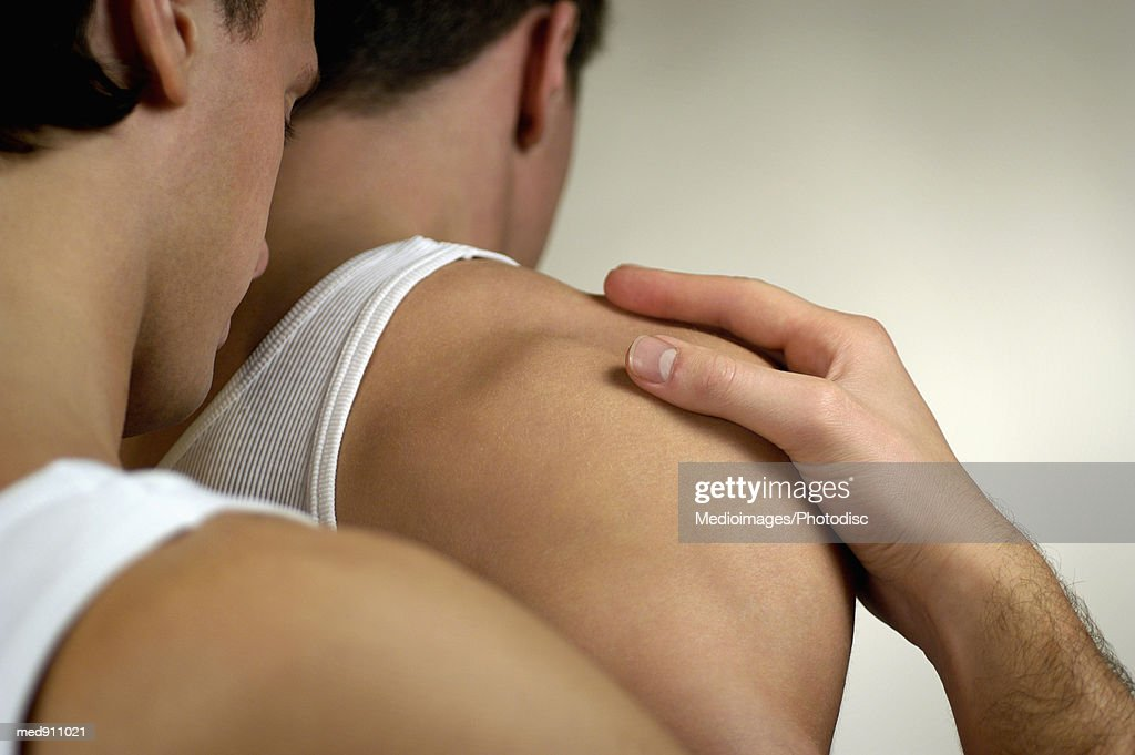 Rear view of a young male couple holding each other : Stock Photo