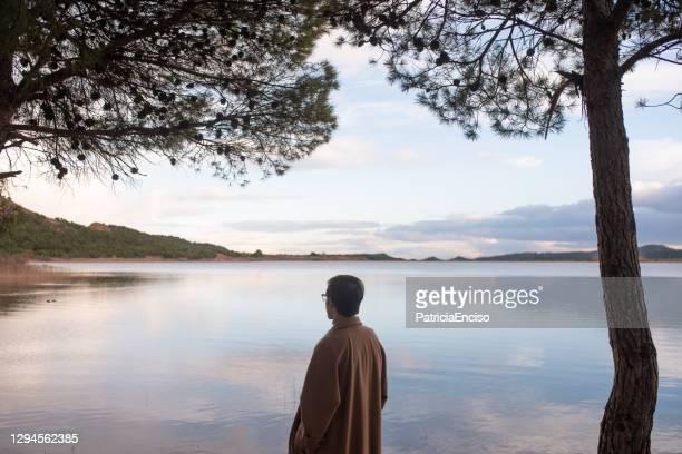 rear view of a young man by a lake - só um homem imagens e fotografias de stock