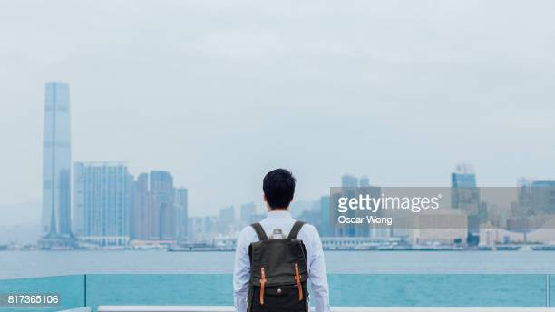 Rear view of a young man by the sea against cityscape