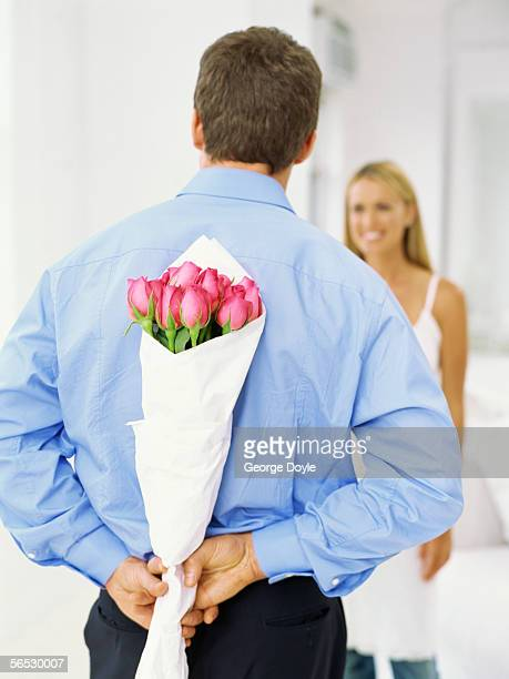 rear view of a young man holding a bouquet of roses behind his back