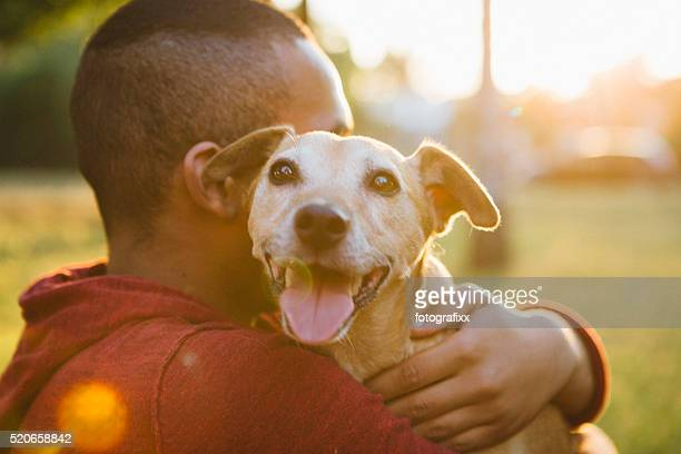 rear view of a young man hug his small dog