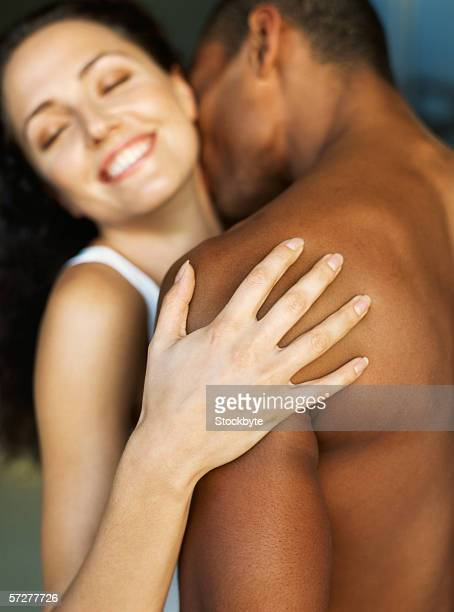 rear view of  a young man kissing a young woman - black men kissing white women stock photos and pictures