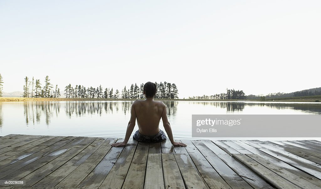 Rear View of a Young Man Looking at the View From a Jetty Across a Lake : Stock Photo