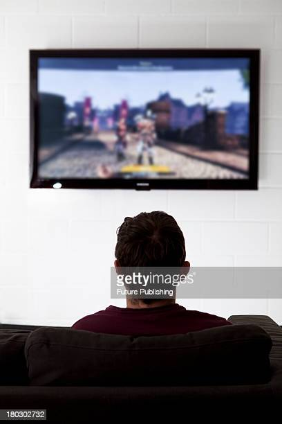 Rear view of a young man on a sofa playing video games on a wallmounted television taken on July 9 2013