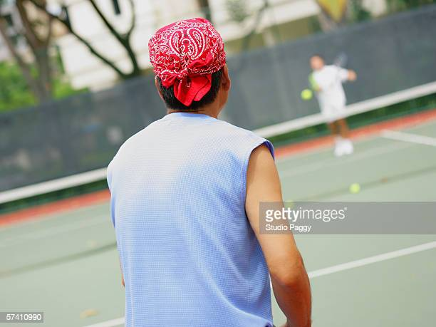 rear view of a young man playing tennis - バンダナ ストックフォトと画像