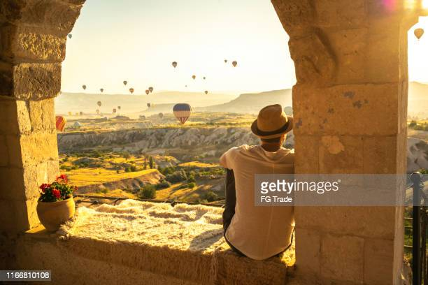 rear view of a young man sitting and looking at view during ballooning festival - wonderlust stock pictures, royalty-free photos & images