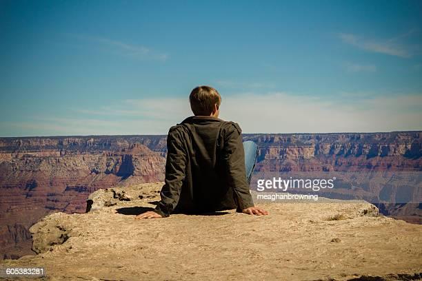 Rear view of a young man sitting on ledge, grand canyon, arizona, america, USA