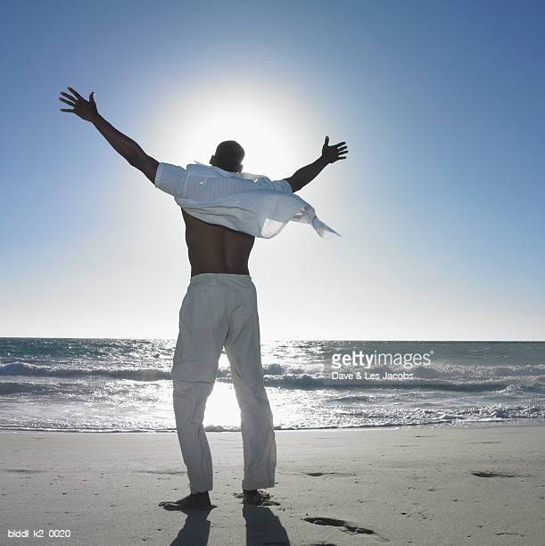Rear view of a young man standing on the beach with his arms outstretched