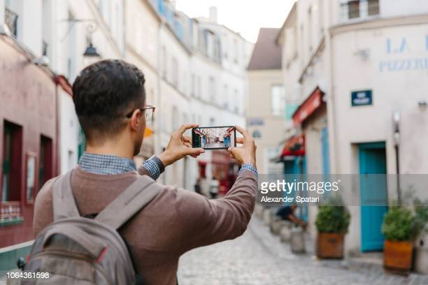 rear view of a young man taking pictures of montmartre street with smart phone, paris, france - photographing stock pictures, royalty-free photos & images