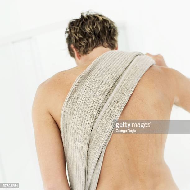 rear view of a young man wiping back with towel - maenner duschen stock-fotos und bilder