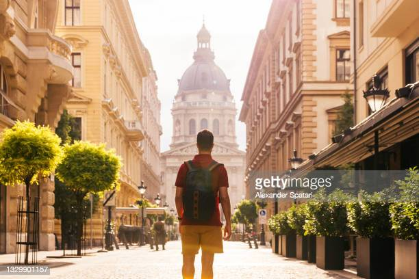 rear view of a young man with backpack exploring the streets of budapest, hungary - traditionally hungarian stock pictures, royalty-free photos & images