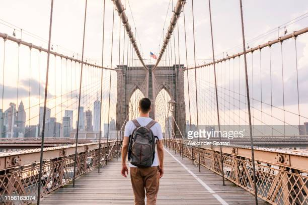 rear view of a young man with backpack walking on brooklyn bridge, new york city, usa - new york city stock-fotos und bilder