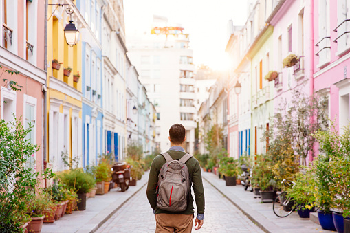 Rear view of a young man with backpack walking on the colorful street - gettyimageskorea