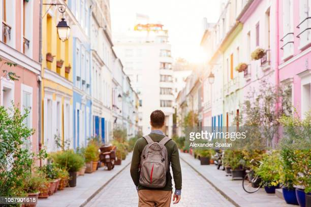 rear view of a young man with backpack walking on the colorful street - al centro foto e immagini stock
