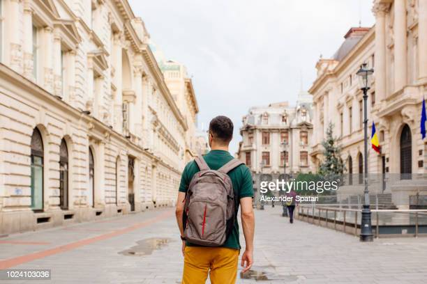 rear view of a young man with backpack walking on the street in the old town of bucharest - rumania fotografías e imágenes de stock