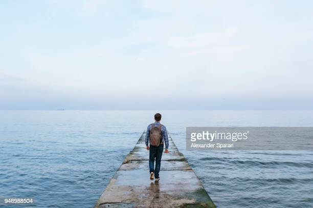 rear view of a young man with backpack walking towards the sea - forschungsreisender stock-fotos und bilder
