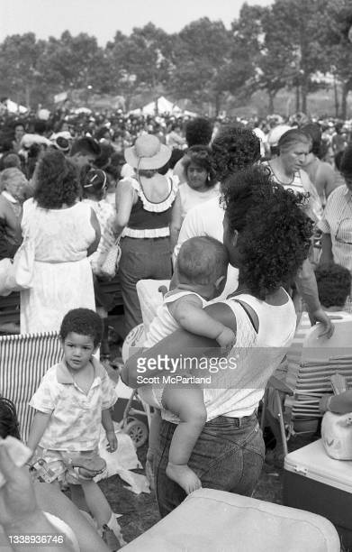 Rear view of a young woman, a baby in her arms, as she stands among a crowd on the lawn in Flushing Meadows Park, in the Corona neighborhood of...