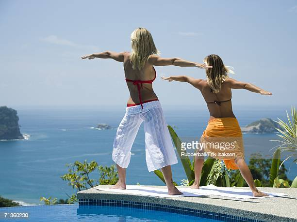 Rear view of a young woman and a mid adult woman practicing yoga at the poolside