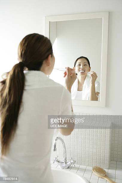 Rear view of a young woman brushing her teeth in front of a mirror