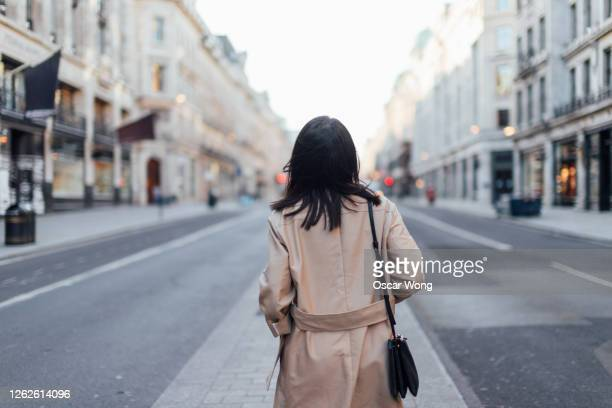rear view of a young woman exploring and discovering regent street, london - back stock pictures, royalty-free photos & images
