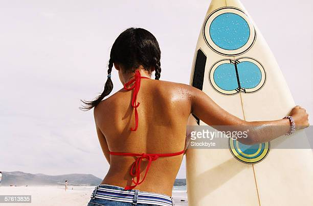 Rear view of a young woman holding a surfboard at the beach
