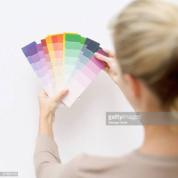 Rear view of a young woman holding color cards against a white wall