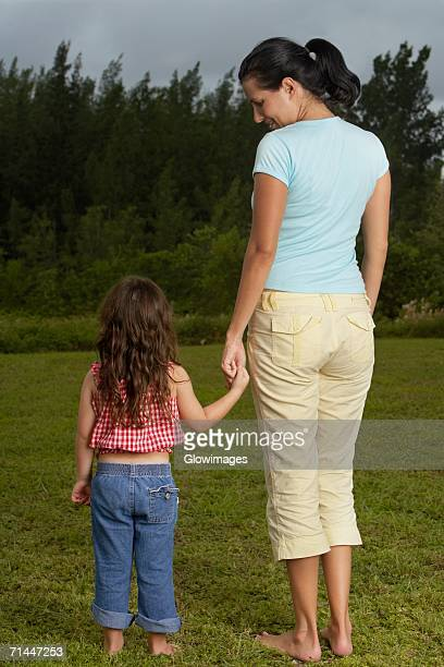 Rear view of a young woman holding her daughter's hand and standing on the lawn