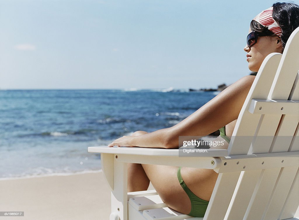 Rear View of a Young Woman in a Bikini Sitting on a Sunlounger on the Beach : Stock Photo