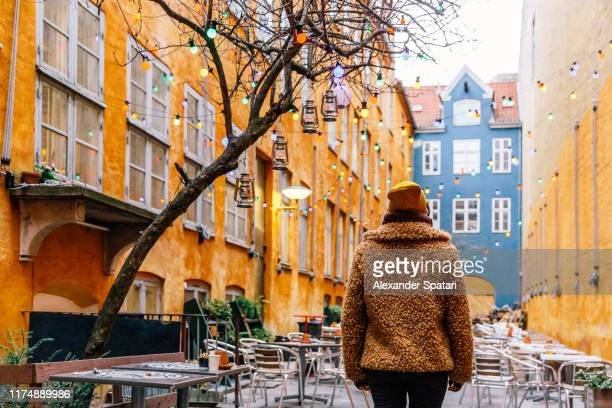 rear view of a young woman in a fake fur coat in the streets of copenhagen, denmark - winter coat stock pictures, royalty-free photos & images