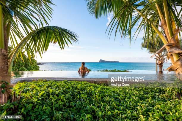 rear view of a young woman in a infinity pool - islas mauricio fotografías e imágenes de stock