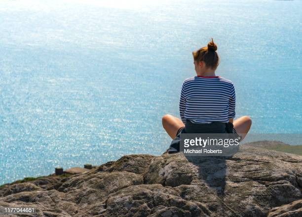 rear view of a young woman looking at the sea from a mountain top - st davids day stock pictures, royalty-free photos & images