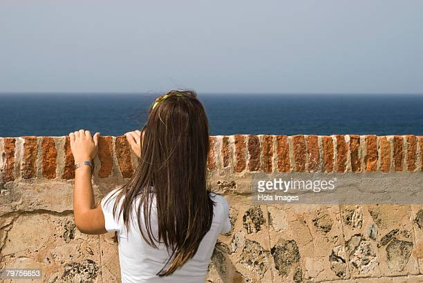 rear view of a young woman looking over a castle wall, morro castle, old san juan, san juan, puerto rico - old san juan wall stock photos and pictures