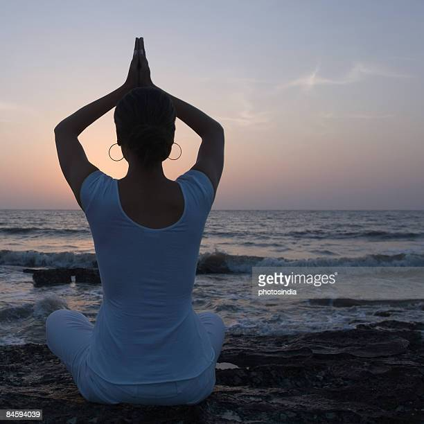 Rear view of a young woman meditating in a prayer position on the beach, Mud Island, Mumbai, Maharashtra, India