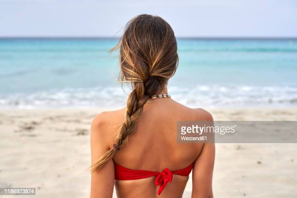 rear view of a young woman on a beach - coiffure photos et images de collection