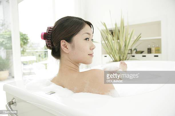 Rear view of a young woman scrubbing her leg in a bubble bath and smiling
