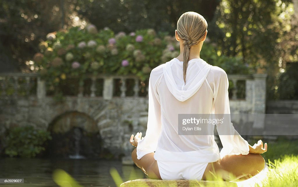 Rear View of a Young Woman Sitting in the Lotus Position by a Lake : Stock Photo