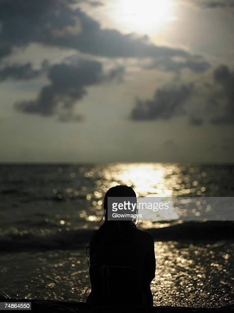 rear view of a young woman sitting on the beach - silueta mujer desnuda fotografías e imágenes de stock